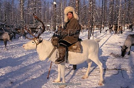 Evenk woman riding reindeer